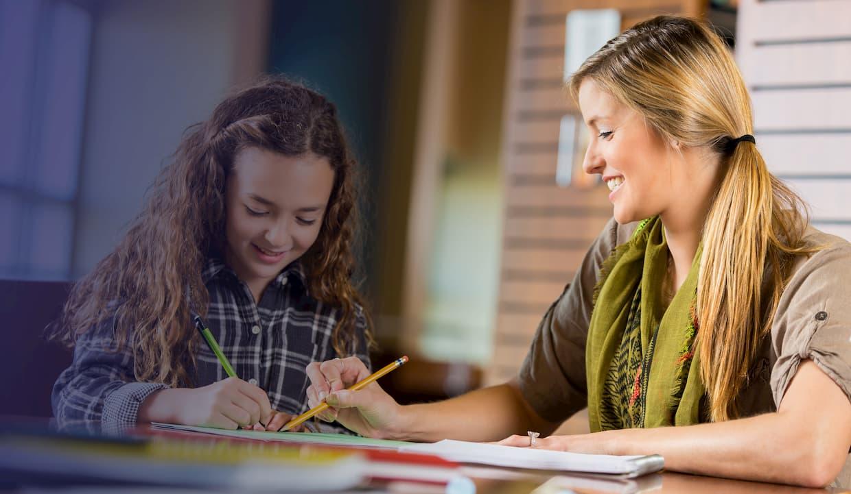 Female blonde tutor tutoring young girl