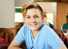 Blonde teenage boy with pencil and mathematics workbook receiving online tutoring