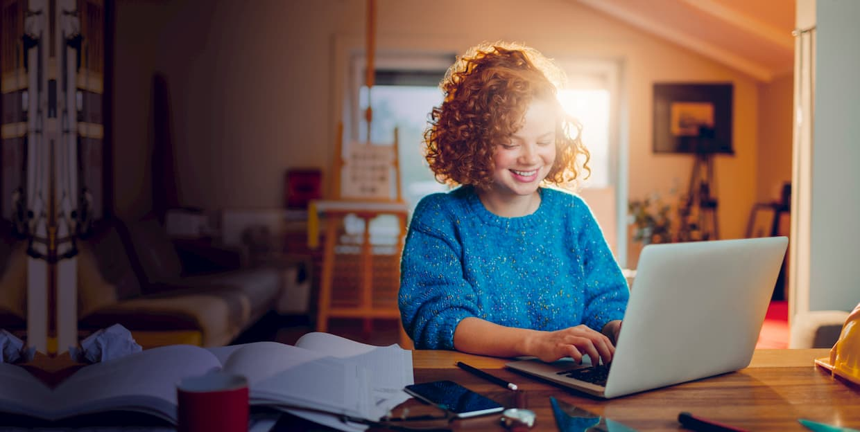 Ginger-haired teenager is looking into her macbook while receiving online mathematics tutoring