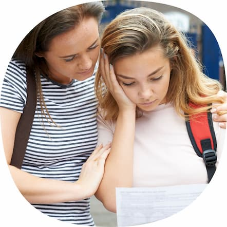 Worried mother and daughter looking at poor exam results